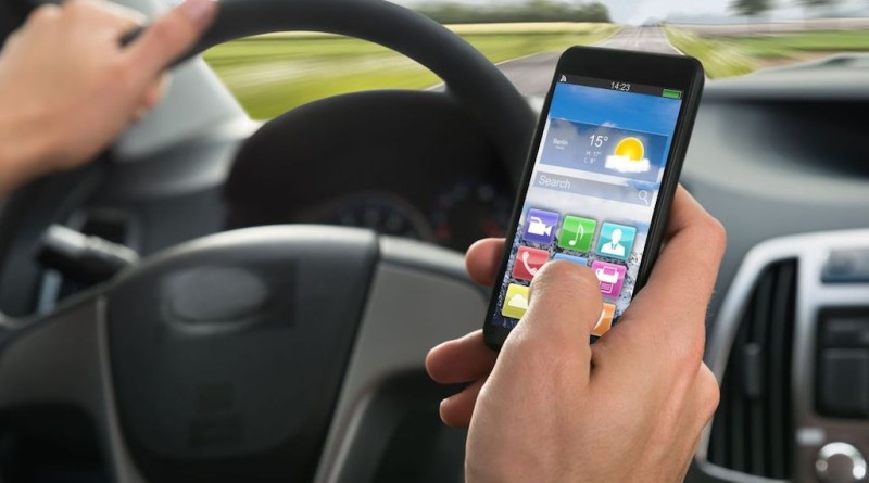 44311839 - close-up of a person's hand using cellphone while driving a car
